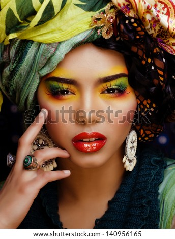 beuty bright woman with creative make up, many shawls on head like cubian woman