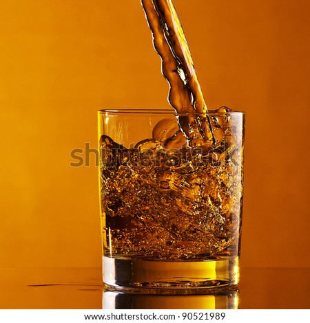 beverage pouring into glass on gold/orange background - stock photo