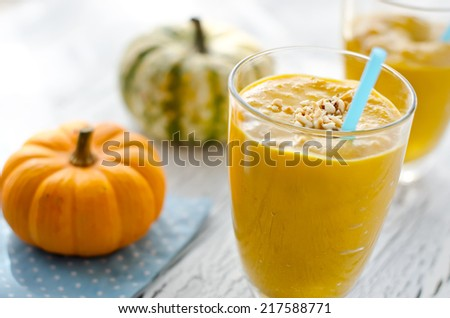 Beverage with pumpkins and milk wooden background - stock photo
