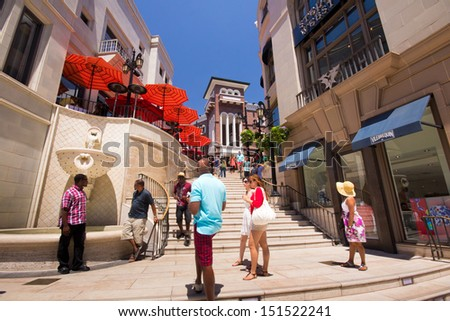 BEVERLY HILLS, CA - AUG 11: Rodeo Drive in Beverly Hills on Aug. 11, 2012. Rodeo Drive is an affluent shopping district known for designer label and haute couture fashion. - stock photo