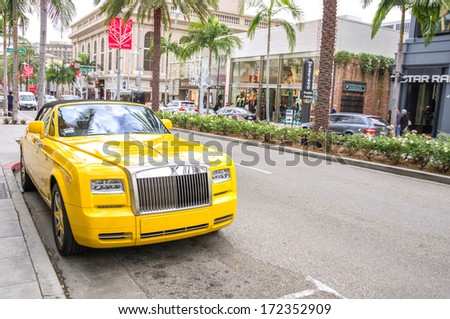 BEVERLY HILLS,CA - DECEMBER 18, 2013: yellow rolls royce at Rodeo Drive,Beverly Hills CA. Rodeo Drive is a shopping district famous for designer label and  couture fashion - stock photo