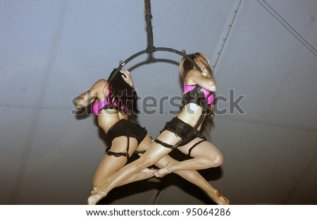 BEVERLY HILLS, CA - FEBRUARY 12: Acrobatic models dancing from the ceiling at the Grammy Party at the Playboy Mansion on February 12, 2012 in Beverly Hills, California. (Photo by Jonathan S. Nowak) - stock photo