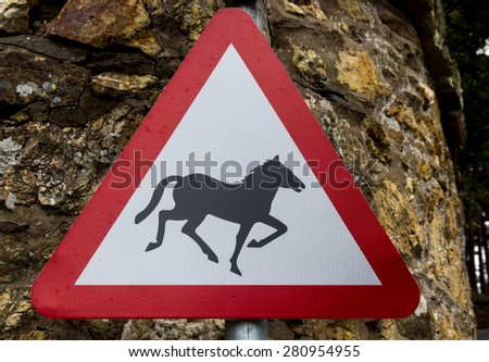 Beware horse or Pony  silhouette. United Kingdom triangular warning sign, warning of quayside or river bank. - stock photo