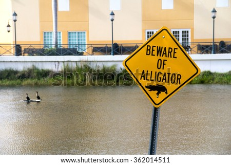 beware of alligator warning caution sign near water - stock photo