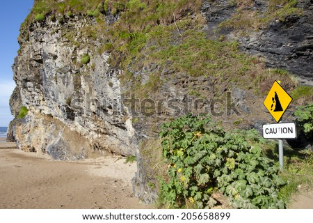 beware of cliff falls warning sign beside the cliffs in Ballybunion county Kerry Ireland - stock photo