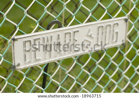 Beware of dog sign on a cloudy day. - stock photo