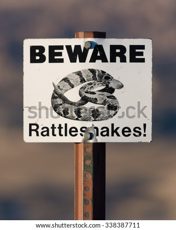 Beware of rattlesnakes sign at the Pinnacles Overlook in Badlands National Park - stock photo