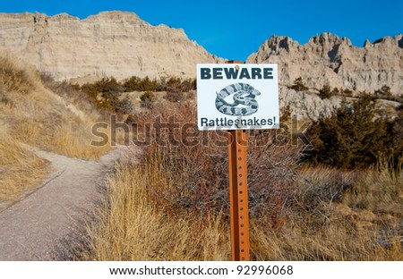 Beware of Rattlesnakes Sign:  Hikers are warned of rattlesnakes in a portion of Badlands National Park. - stock photo