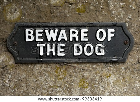 Beware of the dog sign screwed onto stone - stock photo