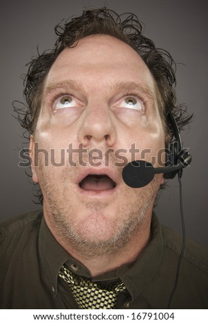 Bewildered Businessman Wearing Phone Headset Against a Grey Background. - stock photo