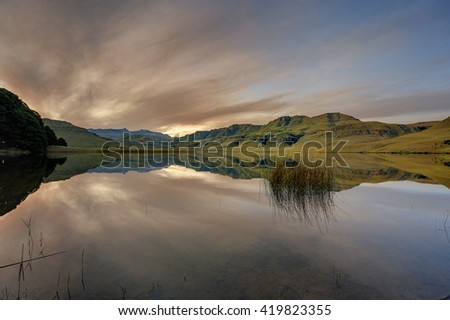 Beyond The Rainbow. 9 image exposure stack of a sun setting over a lake in the Drakensberg mountains. Giant's Cup Wilderness reserve, kwazulu Natal, South Africa - stock photo