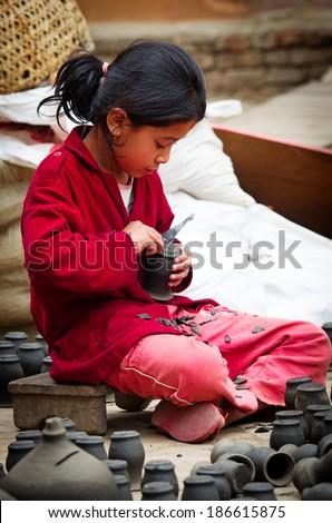 BHAKTAPUR, NEPAL - APR 5: Unidentified Nepalese girl working in the pottery workshop, Apr 5, 2014 in Bhaktapur, Nepal.   - stock photo