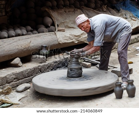 BHAKTAPUR, NEPAL - APR 5: Unidentified Nepalese  potter working in the his pottery workshop, Apr 5, 2014 in Bhaktapur, Nepal.   - stock photo