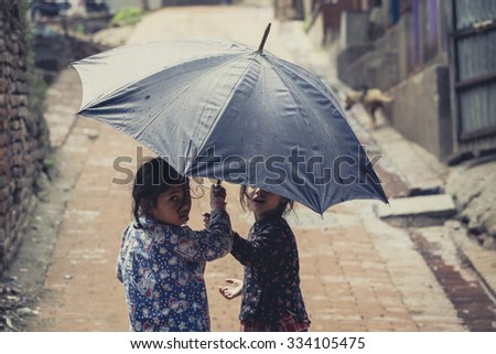 BHAKTAPUR, NEPAL, APRIL 24: Two  Nepalese kids playing with umbrella in the street of Bhaktapur. Nepal 2013.