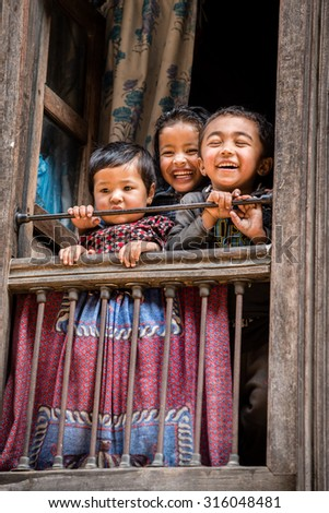 BHAKTAPUR, NEPAL - FEBRUARY 14, 2015: Children laughing and smiling when looking out of a window in Bhaktapur, Nepal.