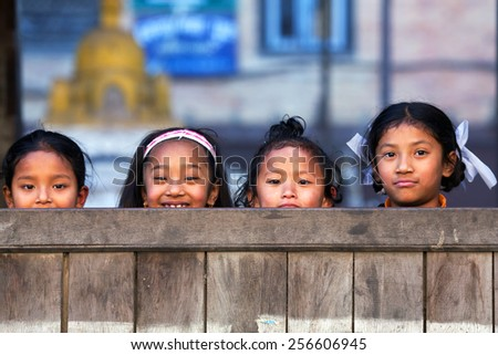 BHAKTAPUR, NEPAL - JANUARY 8: Nepalese schoolgirls pose for a photo during their break time on January 8, 2010 in Bhaktapur, Kathmandu Valley, Nepal. - stock photo