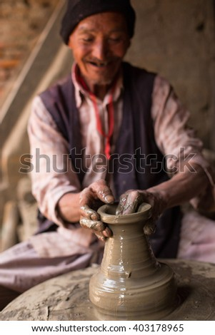 BHAKTAPUR, NEPAL - MARCH 22: Unidentified Nepalese potter working in the his pottery workshop, March 22, 2016 in Bhaktapur, Nepal.  - stock photo