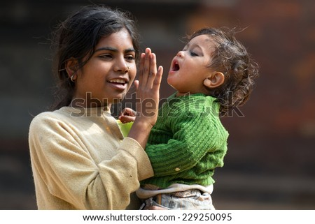BHAKTAPUR, NEPAL, NOVEMBER 25, 2010: A young girl is holding her little sister and putting her hand on her mouth because she's yawning, Bhaktapur, Nepal - stock photo