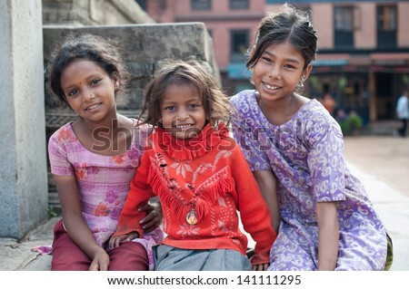 BHAKTAPUR, NEPAL - SEP 29 : Unidentified smiling girls on September 29, 2012 in Bhaktapur, Nepal. Bhaktapur is listed as a World Heritage by UNESCO for its rich culture, temples, and wood artwork. - stock photo