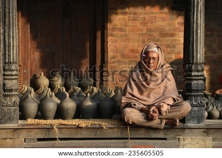 BHAKTAPUR - 13 NOVEMBER: unidentified Nepalese man sits in front of his pottery shop on November 13, 2014 in Bhaktapur, Nepal. Bhaktapur is an ancient city renowned for its elegant pottery art. - stock photo