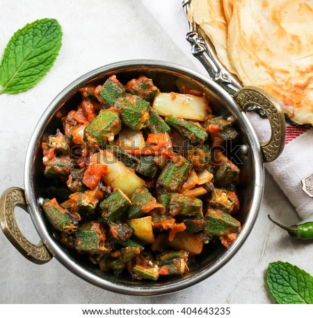 Bhindi Masala / Okra Fry - Deep fried Okra sauteed with tomatoes and spices served with Paratha on side, top down view square composition