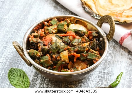 Bhindi Masala / Okra Fry - Popular Indian side dish with okra tomatoes served with Indian Paratha on side, selective focus