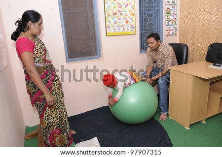 BHOPAL- DECEMBER 7:  A careful mother looks on while her daughter being treated upon for muscular problems in a rehabilitation clinic in Bhopal - India on December 7, 2010. - stock photo