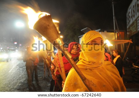 BHOPAL- DECEMBER 2: A Muslim woman carry a torch during the torch rally organized to mark the 26th year of Bhopal gas disaster, in Bhopal - India on December 2, 2010. - stock photo