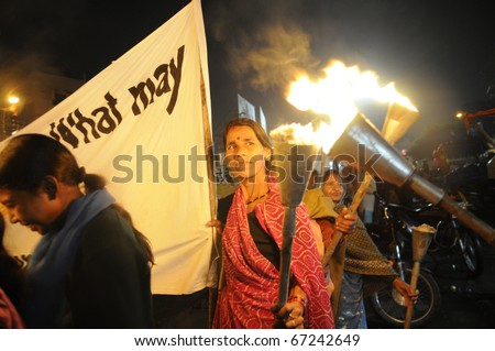 BHOPAL- DECEMBER 2: A woman being given fire for her torch  during the torch rally organized to mark the 26th year of Bhopal gas disaster, in Bhopal - India on December 2, 2010. - stock photo