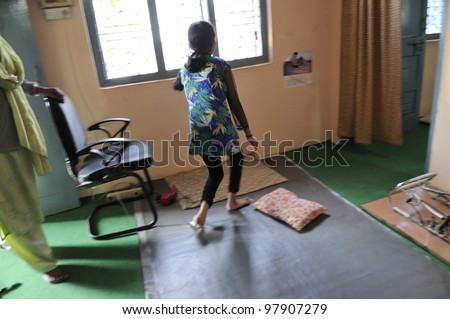 BHOPAL- DECEMBER 7:  An unidentified girl walking with the support of a wall in one of the clinics in Bhopal - India on December 7, 2010. - stock photo