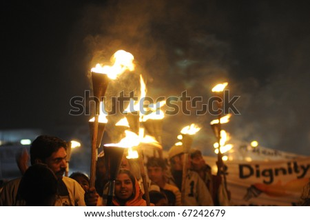 BHOPAL- DECEMBER 2: People carry torches and banners  during the torch rally organized to mark the 26th year of Bhopal gas disaster, in Bhopal - India on December 2, 2010. - stock photo