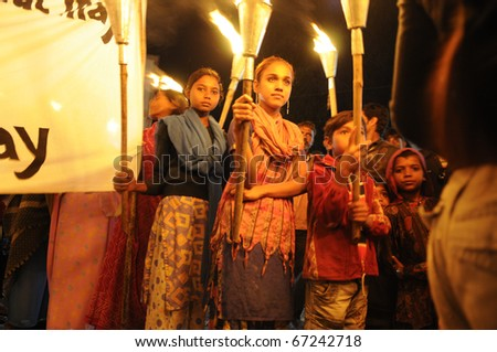 BHOPAL- DECEMBER 2: Protesters hold torches and banner during the torch rally to mark the 26th year of Bhopal gas disaster, in Bhopal - India on December 2, 2010. - stock photo