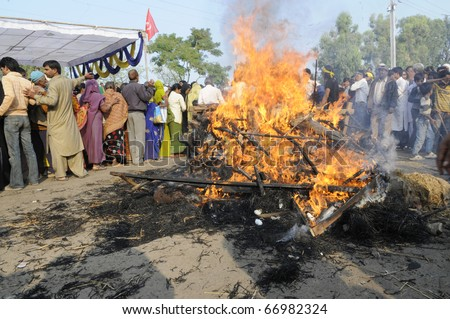 BHOPAL- DECEMBER 3: Protesters in  a circle around the burning effigy during the rally to mark the 26th year of the Bhopal Gas Disaster in Bhopal - India on December 3, 2010.