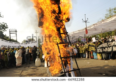 BHOPAL- DECEMBER 3: The burning effigy surrounded by the protesters during the demonstration to mark the 26th Year of the Bhopal Gas Disaster in Bhopal - India on December 3, 2010. - stock photo
