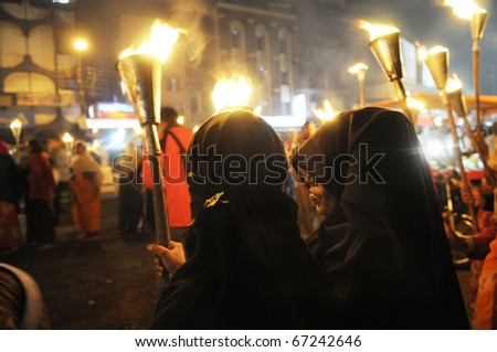 BHOPAL- DECEMBER 2: Two Muslim woman stand on the side of the road  during the torch rally organized to mark the 26th year of Bhopal gas disaster, in Bhopal - India on December 2, 2010. - stock photo