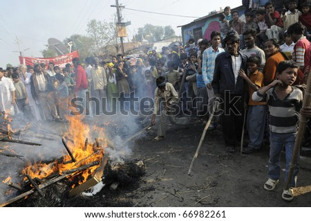 BHOPAL- DECEMBER 3: Yong adults hit the burning effigy with sticks during the rally to mark the 26th Year of the Bhopal Gas Tragedy, in Bhopal - India on December 3, 2010.