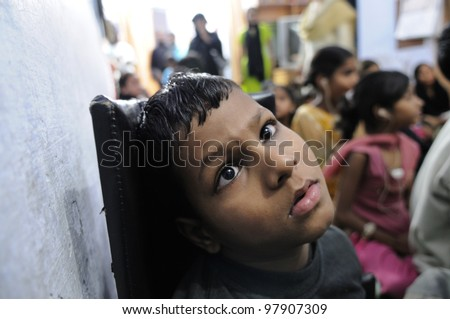 BHOPAL- NOVEMBER 15:  8 years old Aadil suffering from spastic cerebral palsy inside a clinic for the kids of the Bhopal gas victims in Bhopal - India on November 15, 2010. - stock photo