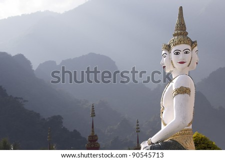 Bhuddistic sculpture with the karst mountains of Laos in the background