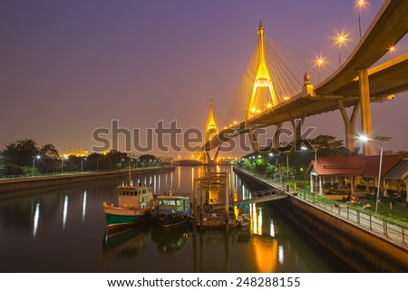 Bhumibol Suspension Bridge across Chao Phraya river with fish boat  at twilight in Bangkok, Thailand - stock photo