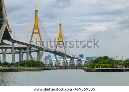 Bhumiphol Highway bridge across the Chaopraya river in Thailand with cityscape background.