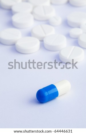 bi-color blue white capsule and tablets on a white background