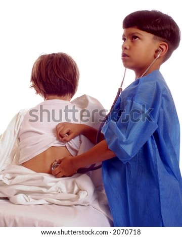 Bi-racial boy in scrubs listening to back of young patient with stethoscope.  Isolated on white.