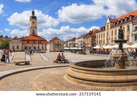 BIALYSTOK, POLAND-JULY 13: People walking on the Kosciusko Main Square with Town Hall on July 13, 2012 in Bialystok, Poland. Bialystok is a historical city with the fastest growth of capital in Poland - stock photo