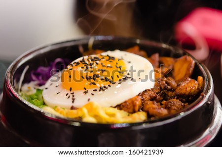 bibimbap in a heated stone bowl  ( rice with meat , mix vegetable and egg )  - stock photo