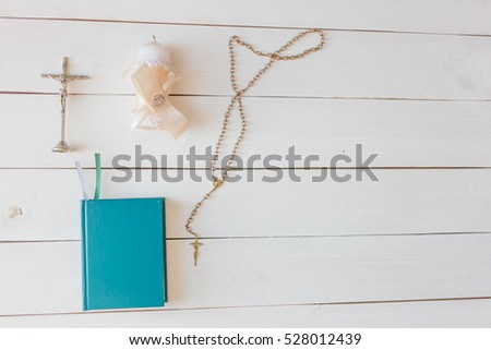 Bible and a rosary on white wooden background. Religion Catholic symbols.Flat lay