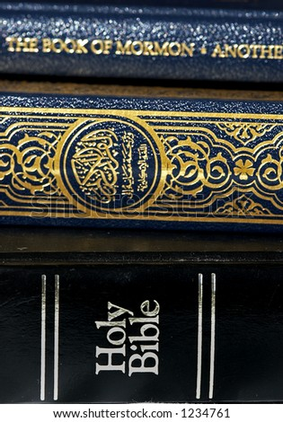 Bible and Koran (Qur'an) and Book of Mormon - stock photo