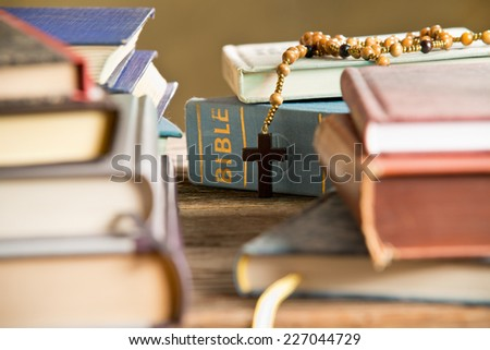 bible  and rosary in the bookshelf - stock photo