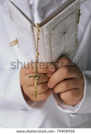 Bible in hands of church alter boy, focus on cross - stock photo