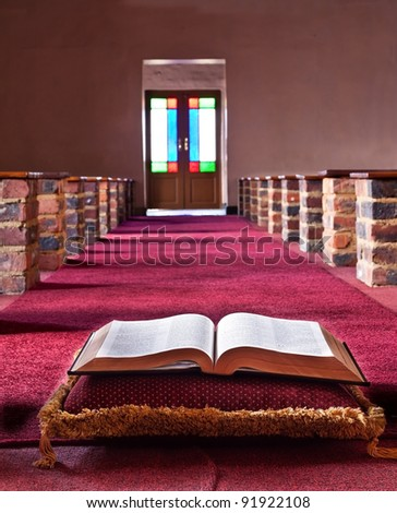 Bible lying on a pillow in a church isle with lead glass doors - stock photo