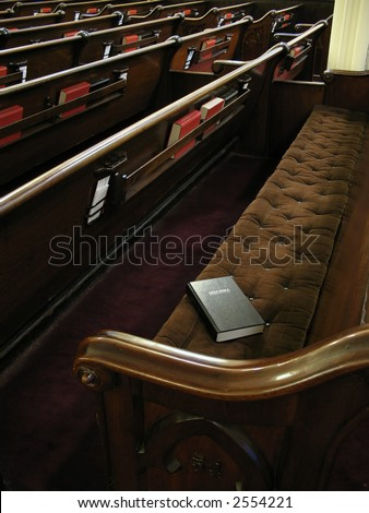 Bible on empty pew. Focused on bible. Empty church with lots of pews.